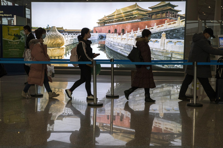 Passengers wearing mask for protection arrive at the airport in Beijing on Sunday, Feb. 9, 2020. China's virus death toll rose above 800, passing the number of fatalities in the 2002-2003 SARS epidemic, but fewer new cases were reported in a possible sign its spread may be slowing as other nations step up efforts to block the disease (AP Photo/Ng Han Guan)