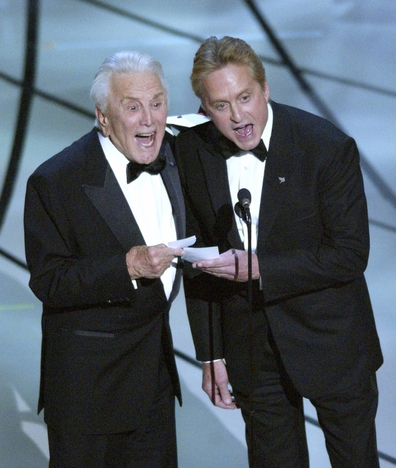 """FILE – This March 23, 2003 file photo shows father-son presenters Kirk Douglas, left, and Michael Douglas shouting out """"Chicago"""" as the best picture of the year at the 75th annual Academy Awards in Los Angeles. Kirk Douglas died Wednesday, Feb. 5, 2020 at age 103. The film starred Michael Douglas' wife Catherine Zeta-Jones, who also won the Oscar for best supporting actress. (AP Photo/Kevork Djansezian, File)"""