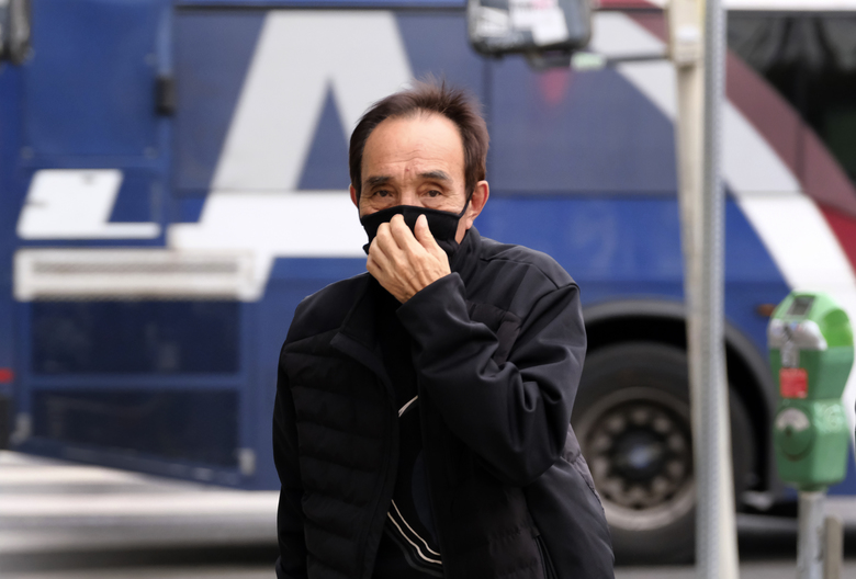 In this Thursday, Feb. 27, 2020, photo, a man crosses the street wearing a protective mask in the Koreatown section of Los Angeles. Fears of the coronavirus combined with the speed and reach of social media can quickly cripple the healthiest of businesses. That's what happened to several Korean restaurants in Los Angeles. Their business was hit hard by false rumors spread on social media that a Korean Air flight attendant with coronavirus dined there last week. (AP Photo/Richard Vogel)