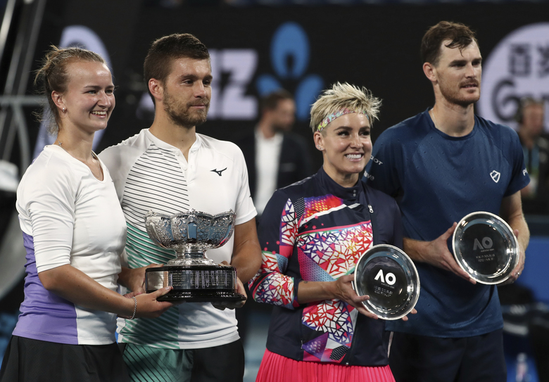 Barbora Krejcikova, left, of the Czech Republic and Croatia's Nikola Mektic, second left, hold their trophy after defeating Bethanie Mattek-Sands, second right, of the U.S. and Britain's Jamie Murray, right, in the mixed doubles final at the Australian Open tennis championship in Melbourne, Australia, Saturday, Feb. 1, 2020. (AP Photo/Dita Alangkara)