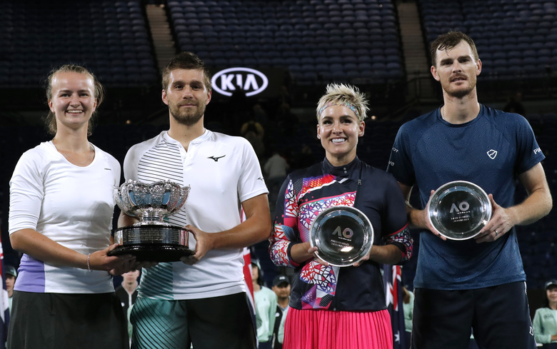 Barbora Krejcikova, left, of the Czech Republic and Croatia's Nikola Mektic, second left, hold their trophy after defeating Bethanie Mattek-Sands, second right, of the U.S. and Britain's Jamie Murray, right, in the mixed doubles final at the Australian Open tennis championship in Melbourne, Australia, Saturday, Feb. 1, 2020. (AP Photo/Lee Jin-man)
