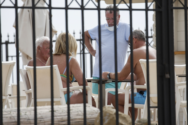 Tourists in quarantine gather at the terrace of the H10 Costa Adeje Palace hotel in La Caleta, in the Canary island of Tenerife, Spain, Thursday, Feb. 27, 2020. Spanish officials say a tourist hotel on the Canary Island of Tenerife has been placed in quarantine after an Italian doctor staying there tested positive for the COVID-19 virus. (AP Photo/Joan Mateu)