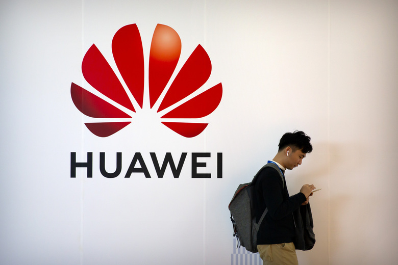 FILE – In this Oct. 31, 2019, file photo, a man uses his smartphone as he stands near a billboard for Chinese technology firm Huawei at the PT Expo in Beijing. Trump administration officials, increasingly intent on preventing China from global technological domination, keep floating the idea that the U.S. government should take a more direct hand in running next-generation 5G wireless networks. (AP Photo/Mark Schiefelbein, File)