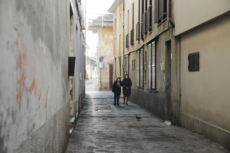 Two women wear masks as they walk in a street in Codogno, near Lodi, Northern Italy, Saturday, Feb. 22, 2020. A dozen towns in northern Italy are on effective lockdown after the new virus linked to China claimed a first fatality in Italy and sickened an increasing number of people. The secondary contagions have prompted local authorities in towns of Lombardy and Veneto to order schools, businesses, and restaurants closed, and to cancel sporting events and Masses. (AP Photo/Luca Bruno)