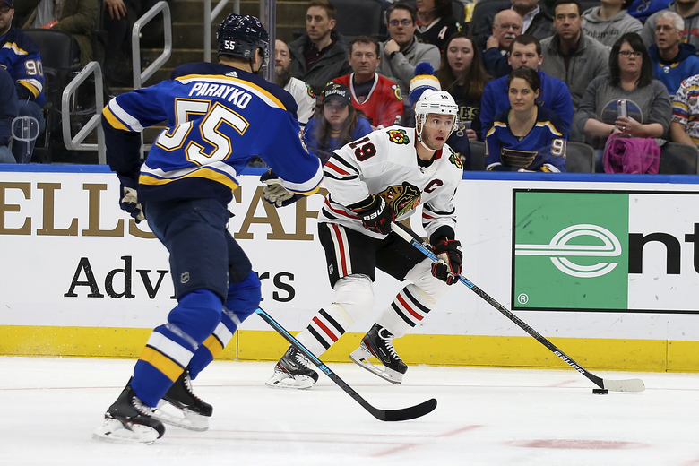 Chicago Blackhawks' Jonathan Toews (19) handless the puck as St. Louis Blues' Colton Parayko (55) defends during the first period of an NHL hockey game Tuesday Feb. 25, 2020, in St. Louis. (AP Photo/Scott Kane)