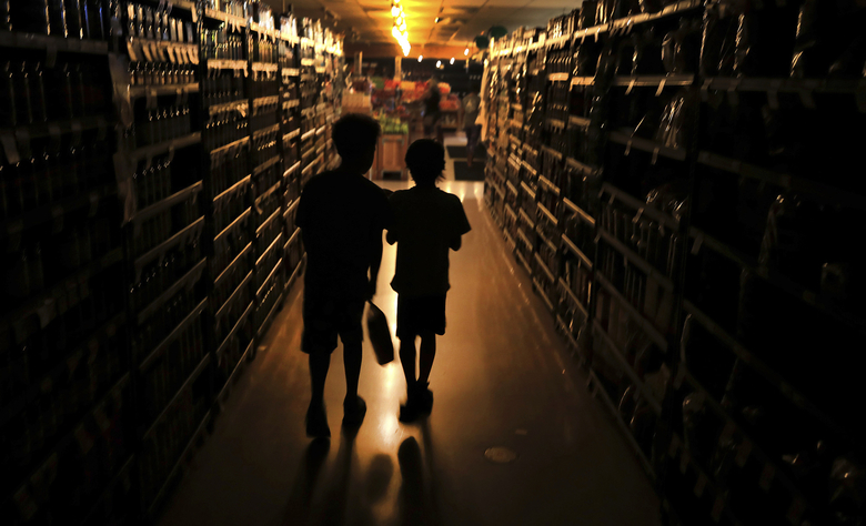 FILE – In this Oct. 23, 2019, file photo, Elijah Carter 11, left, and Robert Haralson, 12, help shop for their parents in a darkened Olivers Supermarket in the Rincon Valley community in Santa Rosa, Calif. The west side of the store was lit by patio lights powered by a generator as power was shut off again by Pacific Gas & Electric Co. due to high fire danger. PG&E is promising on Friday, Jan. 31, 2020, to overhaul its board of directors in an attempt to avoid a potential takeover bid by the state of California and prove the troubled utility is turning over a new leaf as it works through its second bankruptcy in less than 20 years. (Kent Porter/The Press Democrat via AP, File)