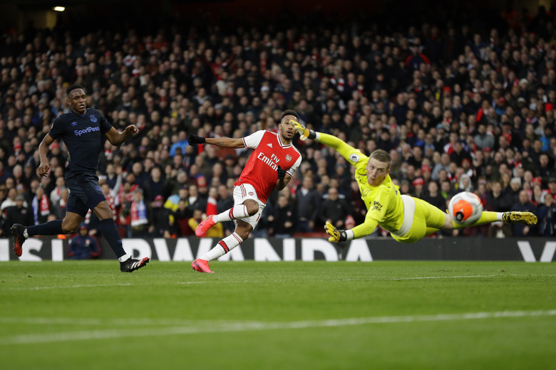 Arsenal's Pierre-Emerick Aubameyang, center, scores his side's second goal as Everton's goalkeeper Jordan Pickford fails to save the ball during the English Premier League soccer match between Arsenal and Everton at Emirates stadium in London, Sunday, Feb. 23, 2020. (AP Photo/Kirsty Wigglesworth)