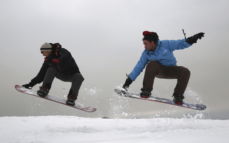 In this Friday, Jan. 24, 2020 photo, Ahmad Sorush, 22, left, and Nizaruddin Alizada, 20, make a jump on the snow-covered hillside known as Kohe Koregh, on the outskirts of Kabul, Afghanistan. While Afghanistan's capital may seem an unlikely destination for snowboarders, a group of young Afghans is looking to put the city on the winter sports map and change perceptions about their war-weary nation. (AP Photo/Rahmat Gul)