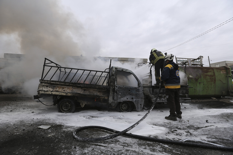 Firefighters hose a truck after a government airstrike in the city of Idlib, Syria, Tuesday, Feb. 11, 2020. The latest violence in Idlib came as government forces came closer to capturing the last rebel-held part of a strategic highway linking southern and northern Syria, which would bring the road under Syrian President Bashar Assad's full control for the first time since 2012. (AP Photo/Ghaith Alsayed)