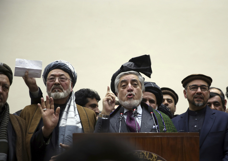 Afghan presidential candidate Abdullah Abdullah, center, addresses the media following a conference with his party members in Kabul, Afghanistan, Tuesday, Feb. 18, 2020. Afghanistan's independent election commission says Ashraf Ghani has won a second term as president, more than four months after polls closed. (AP Photo/Rahmat Gul)