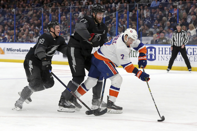 Tampa Bay Lightning's Ondrej Palat, left, of Czech Republic and Victor Hedman, of Sweden, check New York Islanders' Jordan Eberle during the second period of an NHL hockey game Saturday, Feb. 8, 2020, in Tampa, Fla. (AP Photo/Mike Carlson)