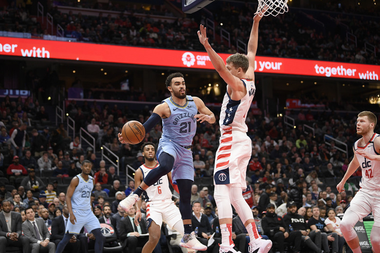 Memphis Grizzlies guard Tyus Jones (21) looks to pass next to Washington Wizards forward Moritz Wagner, center right, during the first half of an NBA basketball game, Sunday, Feb. 9, 2020, in Washington. (AP Photo/Nick Wass)