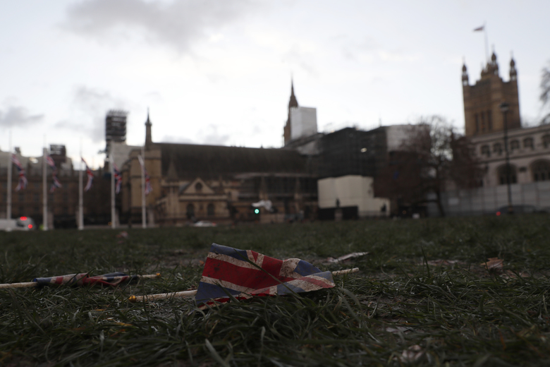 A British Union flag from Brexit day celebrations lies in the grass in front of the Palace of Westminster in London, early Saturday, Feb. 1, 2020. Britain officially left the European Union on Friday after a debilitating political period that has bitterly divided the nation since the 2016 Brexit referendum. (AP Photo/Alastair Grant)