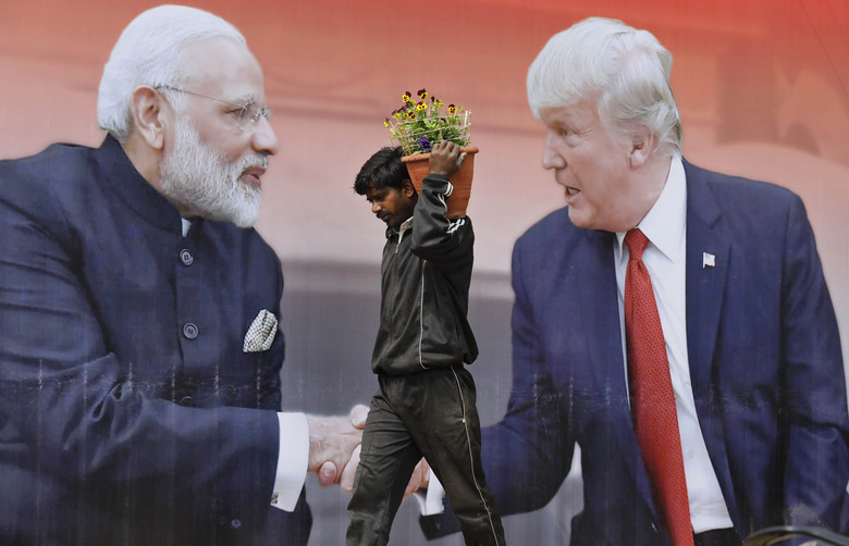 An Indian worker carries flowers to plant past a billboard featuring U.S. President Donald Trump and Indian Prime Minister Narendra Modi in Agra, India, Sunday, Feb. 23, 2020, a day before Trump travels to Agra to visit the 17th century monument to love, the Taj Mahal. (AP Photo/Rajesh Kumar Singh)