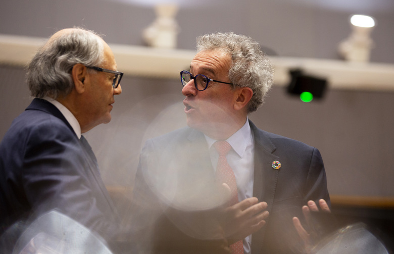 Luxembourg's Finance Minister Pierre Gramegna, right, speaks with Malta's Finance Minister Edward Scicluna during a meeting of EU finance ministers at the Europa building in Brussels, Tuesday, Feb. 18, 2020. EU finance ministers meet Tuesday to discuss tax havens. (AP Photo/Virginia Mayo)
