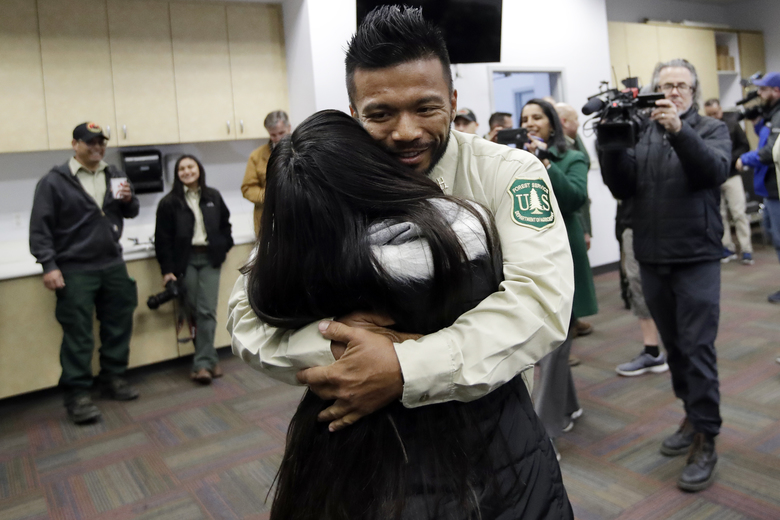 Firefighter Leonard Dimaculangan, of Pasadena, Calif. hugs his daughter Promise, 11, after arriving from a deployment fighting wildfires in Australia Wednesday, Feb. 5, 2020, in Los Angeles. 20 firefighters from the Angeles National Forest worked with the Victoria Rural Fire Service to fight the blazes that are consuming Australia. (AP Photo/Marcio Jose Sanchez)