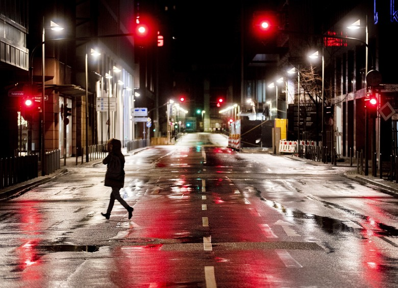 A woman crosses a deserted street in central Frankfurt, Germany, Monday, Feb. 10, 2020. A heavy storm with rain hits big parts of Germany. (AP Photo/Michael Probst)