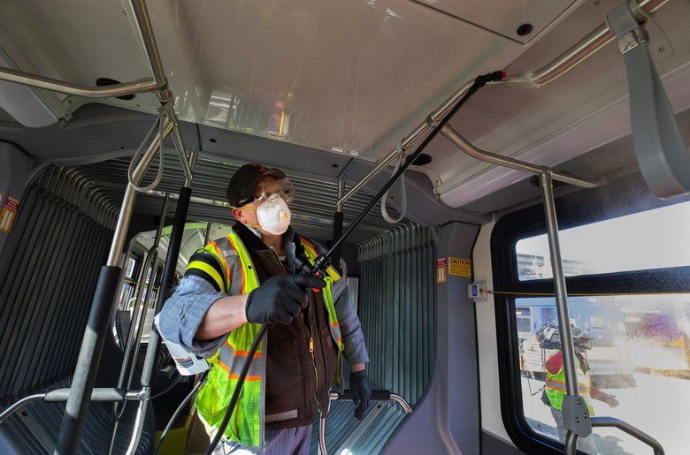 Larry Bowles, an equipment service worker with King County Metro, sprays Virex solution in the interior of one of Metro's 1,600 buses at a maintenance base in Sodo on Wednesday.  The sprayers are a lot quicker than using hand wipes and contain chemicals that are gentler on people than chlorine. It takes from one to two minutes to spray the entire interior of a bus. (Ellen M. Banner / The Seattle Times)