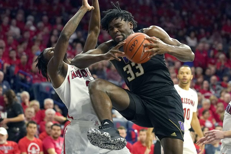 Washington forward Isaiah Stewart drives on Arizona guard Dylan Smith (3) during the first half of an NCAA college basketball game Saturday, March 7, 2020, in Tucson, Ariz. Smith broke his nose on the play. (Rick Scuteri / The Associated Press)