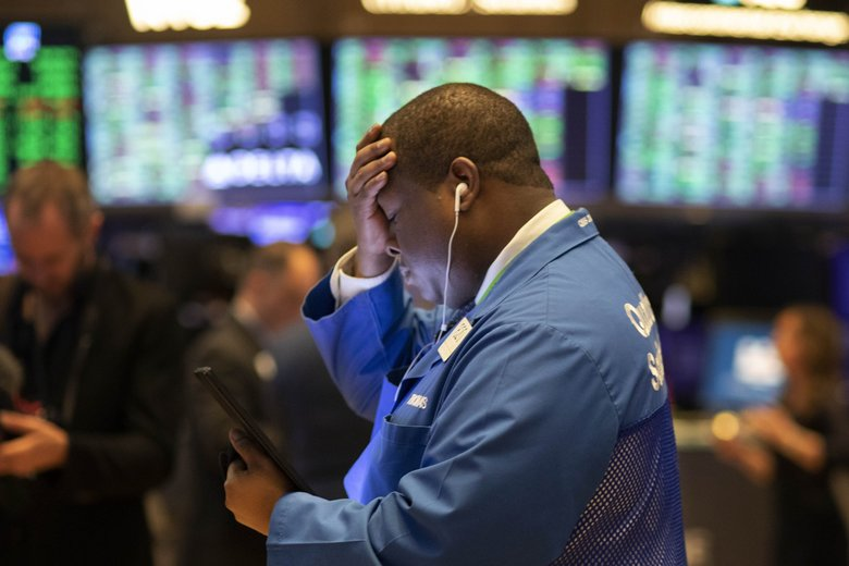 Stock trader Thomas Lee works at the New York Stock Exchange Friday. Stocks made a small comeback a day after the worst drop since 1987. (Mark Lennihan / AP)
