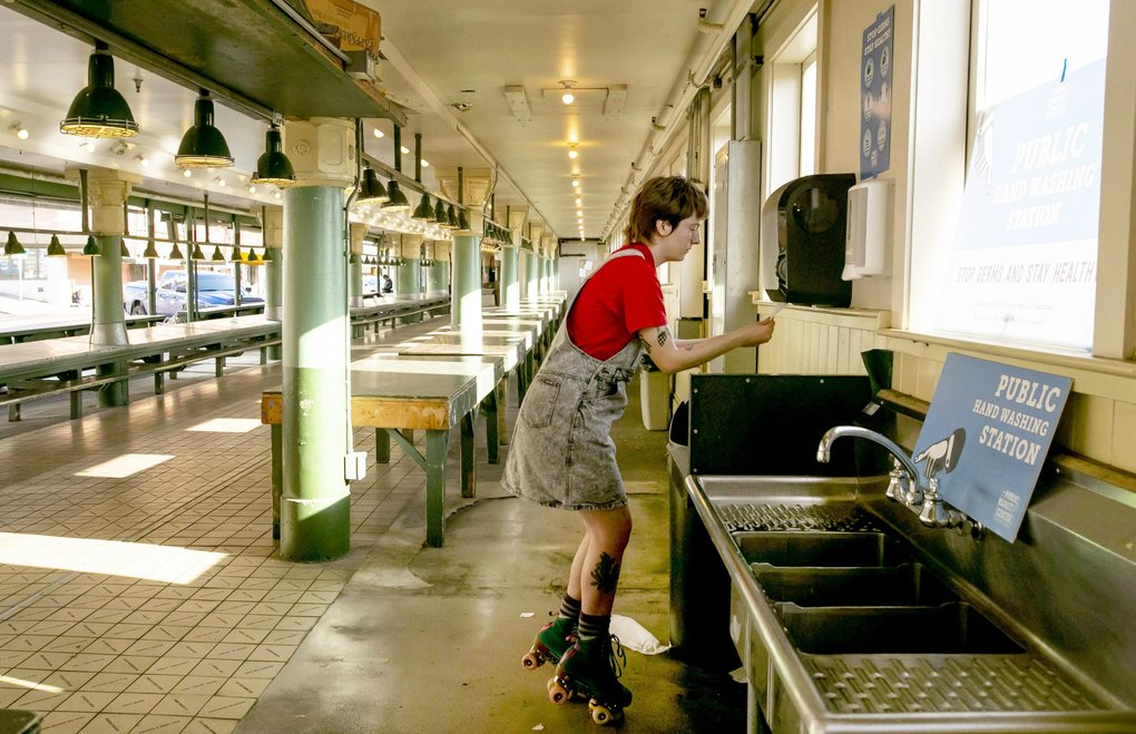 "Fiona Fitzpatrick stopped skating through a deserted Pike Place Market on Wednesday long enough to wash her hands — one of the measures public health officials recommend doing to slow the spread of novel coronavirus, SARS-CoV-2. Fitzpatrick says roller-skating is one example of an activity she ""can totally do alone,"" and meets the one of the other criteria experts urge during the pandemic: social distancing. She usually works as a dog walker,  but is now down to one client. (Erika Schultz / The Seattle Times)"