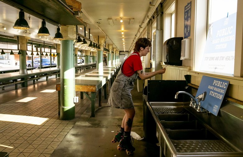 "Fiona Fitzpatrick, washes her hands while roller skating through an empty Pike Place Market  on Wednesday. Fitzpatrick says roller skating is one example of an activity she can ""can totally do alone,"" and practice social distancing. She works a dog walker, known as @skateyourdog on Instagram, but is now down to one client. (Erika Schultz / The Seattle Times)"