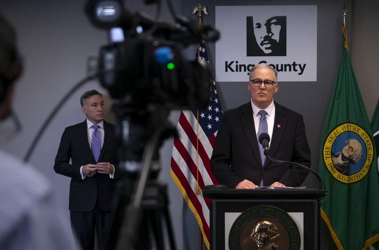 Washington state governor Jay Inslee, center, talks at a press conference about the coronavirus outbreak in downtown Seattle Monday, March 16, 2020.  King County Executive Dow Constantine is at left. Terry Dockter, on-camera ASL interpreter, is at right.  (Erika Schultz / The Seattle Times)