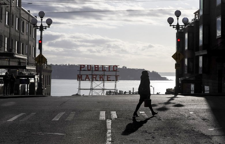 A woman walks near Pike Place Market on Thursday as downtown Seattle streets become quieter and less packed with cars and people. Many local restaurants are beginning to close due to lack of business downtown.  Time stamp: 5:28 p.m.  On Thursday, March 12, 2020. 213326 213326