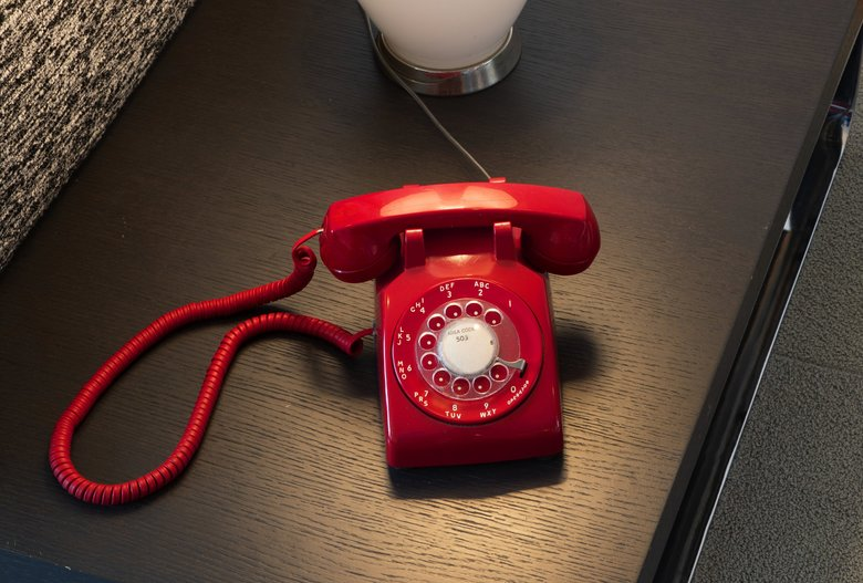 """A working retro telephone adds a pop of bright color — and a distinctive sound — to the Browns' living room. """"We have a landline because I want to hear it ring,"""" says Stina, who found the phone on eBay. (Turns out the seller lived in nearby Queen Anne.) (Mike Siegel / The Seattle Times)"""