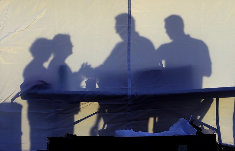Medical personnel are silhouetted against the back of a tent before the start of coronavirus testing in the parking lot outside of Raymond James Stadium early Wednesday, March 25, 2020, in Tampa, Fla. The testing is being done by appointment only. (AP Photo/Chris O'Meara) FLCO101 FLCO101