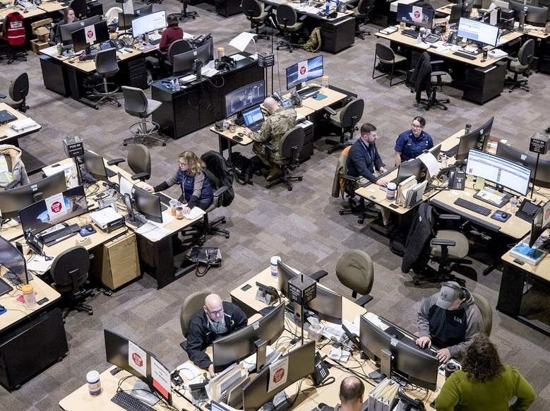 Paper stop signs adorn some work stations on the State Emergency Operations Center floor, where officials are coordinating response to the coronavirus, to ensure social distancing and slow the spread of coronavirus.(Amanda Snyder / The Seattle Times)