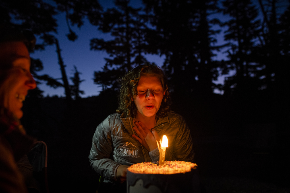Watched by See You at the Summit founder Heather Rose Otto, Josie Alldredge laughs while trying to blow out the candle on her Unicorn Poop Cake on the night of her 18th birthday, in the wilderness. (Joshua Bright)