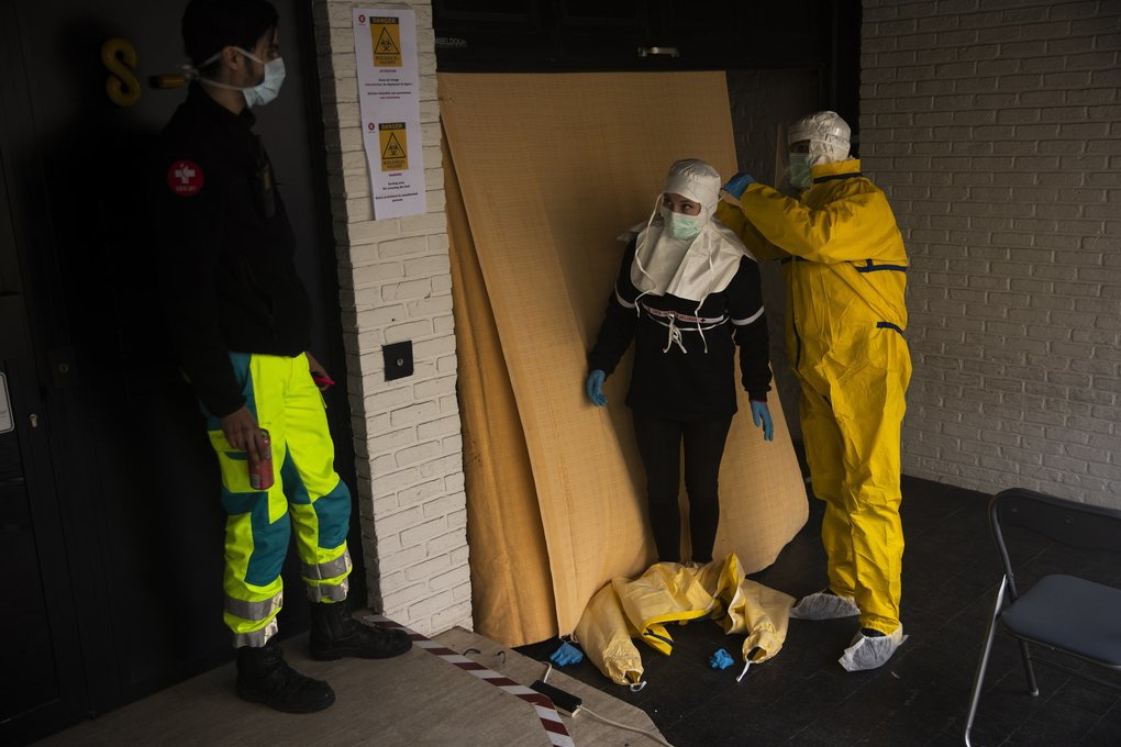 In Brussels, a member of the medical staff, wearing full protective equipment, helps a co-worker to remove her protective suit in the triage area of the polyclinic Klinicare during a partial lockdown against the spread of Covid-19 on Monday, March 30, 2020. (Francisco Seco / The Associated Press)