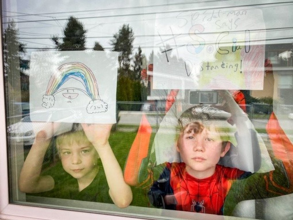 "Lucas Gramer, 6, and his brother Brett, 8, hold up artwork to their window. They're part of a project called ""From Out to In"" that West Seattle photographer Cat Cassidy is working on to document our distant togetherness via shots of neighbors smiling through their windows. (Cat Cassidy)"