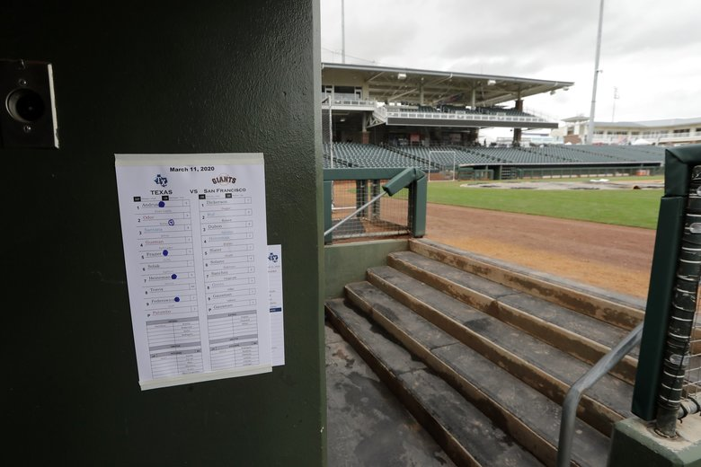 A line-up sheet from the previous day's baseball game is posted on the wall of an otherwise empty dugout and ballpark after the cancellation of the spring training baseball game between the Kansas City Royals and the Seattle Mariners Thursday, March 12, 2020, in Surprise, Ariz. Major League Baseball is delaying the start of its season by at least two weeks because of the coronavirus outbreak and has suspended the rest of its spring training game schedule. (AP Photo/Elaine Thompson) AZET105 AZET105 (Elaine Thompson / The Associated Press)