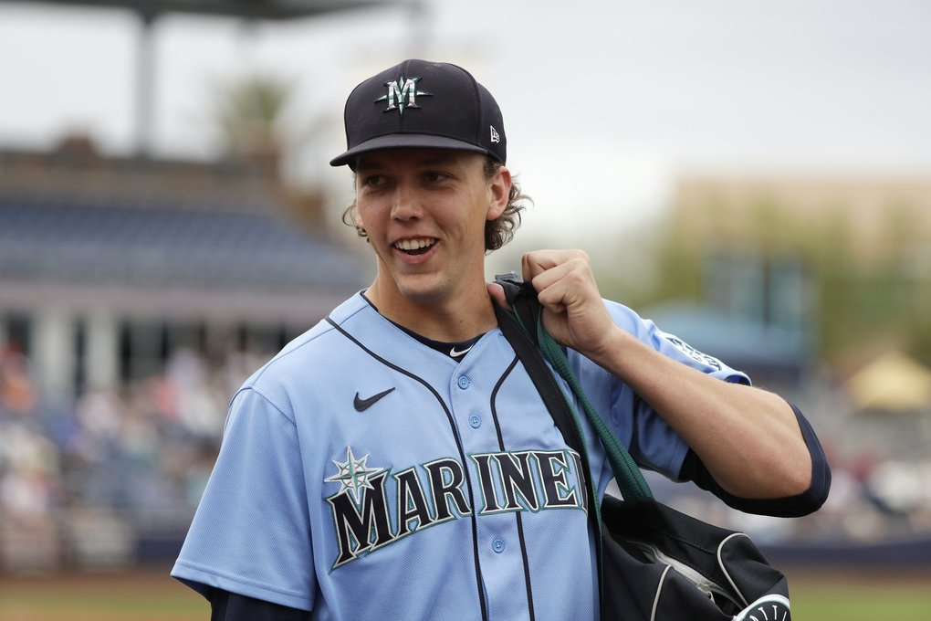 Seattle Mariners starting pitcher Logan Gilbert smiles at a friend as he heads off the field after throwing against the Los Angeles Angels during a spring training baseball game Tuesday, March 10, 2020, in Peoria, Ariz. (Elaine Thompson / The Associated Press)