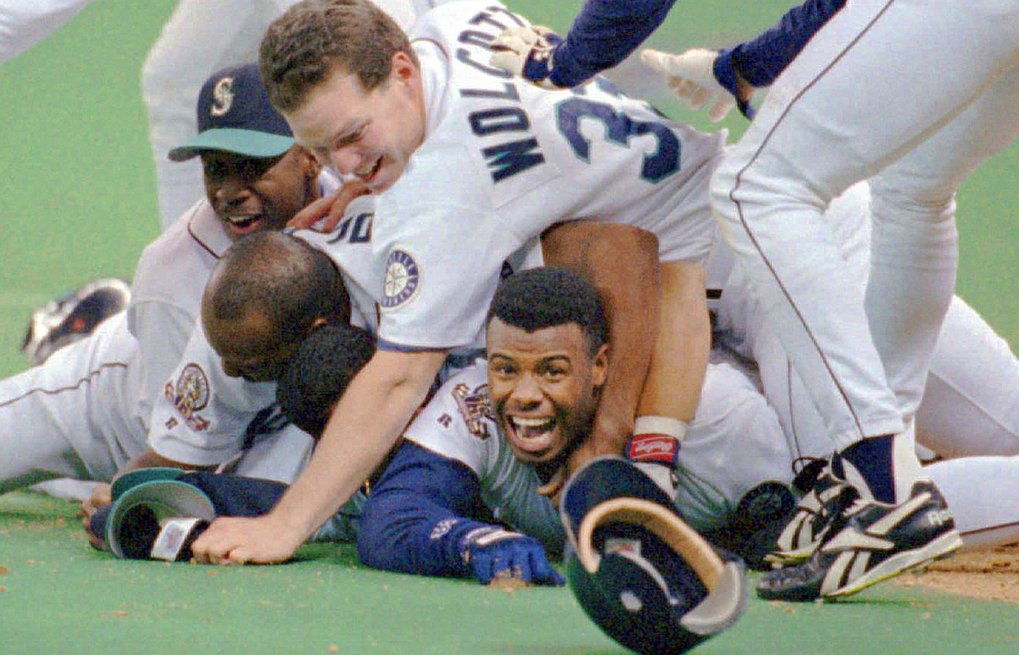 Seattle Mariners' Ken Griffey Jr. smiles from beneath a pile of teammates who mobbed him after he scored the winning run in the bottom of the 11th inning of Game 5 of the ALDS against the New York Yankees in Seattle, October 8, 1995. (Elaine Thompson / The Associated Press)