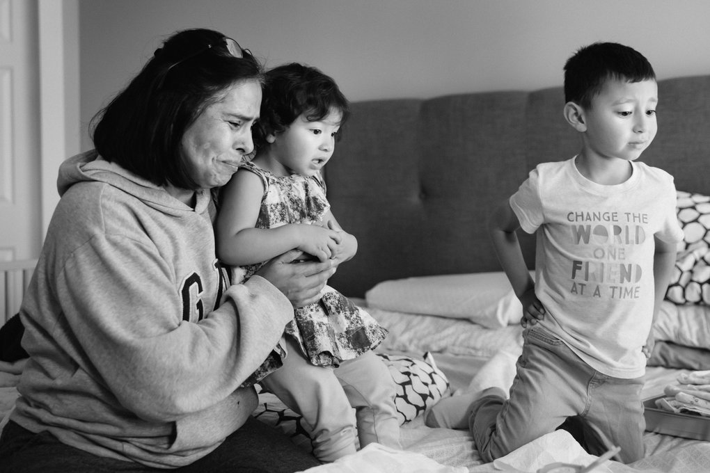 Elena Quezada holds her grandkids, Sophia and Vincent, while they watch their mom in labor with their baby sister Lucia at their home. Quezada is Angelica Grunewald's mother. (Bettina Hansen / The Seattle Times)