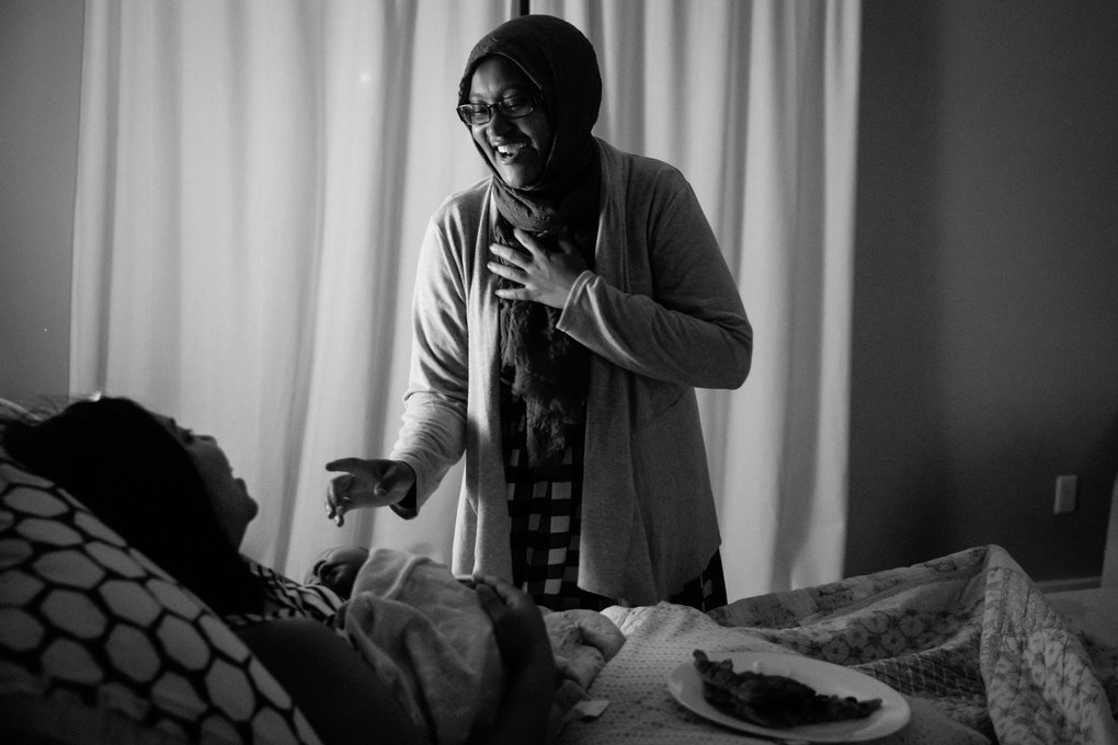Licensed midwife Faisa Farole says goodnight to Angelica Grunewald, nursing baby Lucia in her bed at home, about three hours after her birth. (Bettina Hansen/ The Seattle Times)