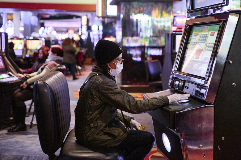 A gambler wearing a face mask and gloves at the Resorts World Casino in Queens, March 8, 2020. The New York Racing Authority said it would review its security protocols after thieves stole more than $200,000 at the adjacent Aqueduct Racetrack on Saturday night. (Sarah Blesener/The New York Times)