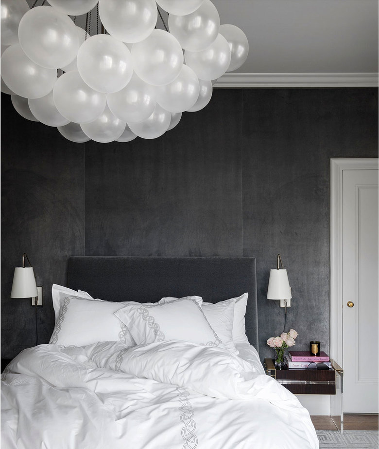 Alison Pickart designed this bedroom in San Francisco with upholstered walls in dark gray silk velvet for a soft touch and noise dampening. Bed linens are kept simple and luxe. The Cloud chandelier is by Apparatus. (Aaron Leitz)