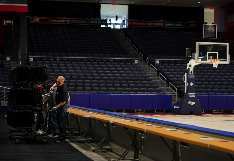 Workers remove chairs from media row inside an arena  in Dayton, Ohio, on Friday as the college season ended. (Aaron Doster / The Associated Press)