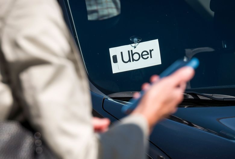 A traveler uses a smartphone in front of a vehicle displaying Uber Technologies Inc. signage at the Oakland International Airport. (David Paul Morris/Bloomberg)