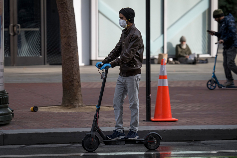 A person wearing a protective mask and gloves rides a scooter on Market Street in San Francisco recently. (David Paul Morris / Bloomberg).