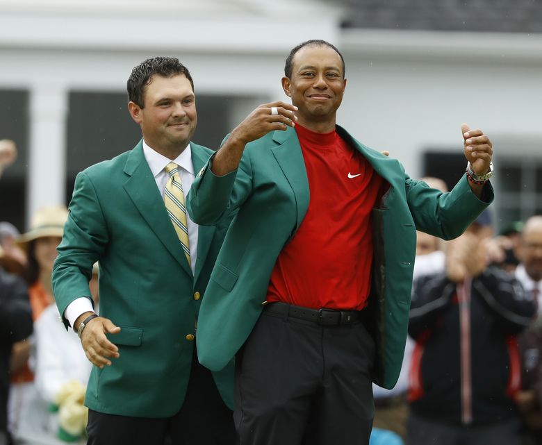 FILE – In this April 14, 2019, file photo, Patrick Reed, left, helps Tiger Woods with his green jacket after Woods won the Masters golf tournament, in Augusta, Ga. The annual rite of spring for golf won't happen this year. The Masters has been postponed until a later date. Augusta National did not indicate when the Masters would be played. That means there will be no golf at least for the next month. The Masters began in 1934 and only World War II has kept it from being played. This was the biggest shoe to drop for golf. The PGA Tour already canceled the next three events leading up to the Masters. Tiger Woods was to be going after his sixth green jacket. (AP Photo/Matt Slocum, File)