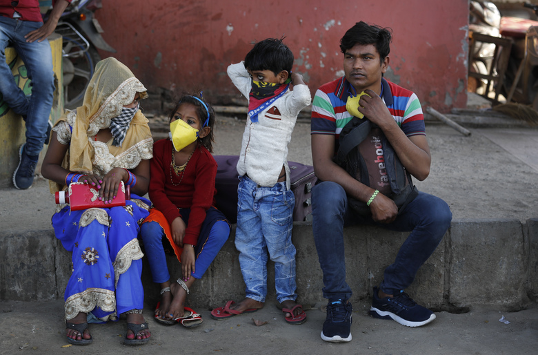 Migrant daily wage laborer Ram Bhajan Nisar and his family wait for transportation to travel to their hometown following a lockdown amid concern over spread of coronavirus in New Delhi, India, Friday, March 27, 2020. Some of India's legions of poor and others suddenly thrown out of work by a nationwide stay-at-home order began receiving aid on Thursday, as both public and private groups worked to blunt the impact of efforts to curb the coronavirus pandemic. The measures that went into effect Wednesday, the largest of their kind in the world, risk heaping further hardship on the quarter of the population who live below the poverty line and the 1.8 million who are homeless. (AP Photo/Manish Swarup)