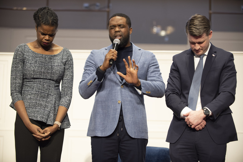 In this Saturday, Feb. 22, 2020 photo, incumbent Cook County State's Attorney Kim Foxx, left,  prays with Senior Pastor, Rev. Dr. Charles E. Dates, center, and candidate Bill Conway, right, at the 2020 Primary Candidates' Forum at the Progressive Baptist Church in Chicago. The Chicago area's top prosecutor is trying to convince voters of her criminal justice reform record as she faces continued questions about her handling of actor Jussie Smollett's case. (Colin Boyle/Chicago Sun-Times via AP)