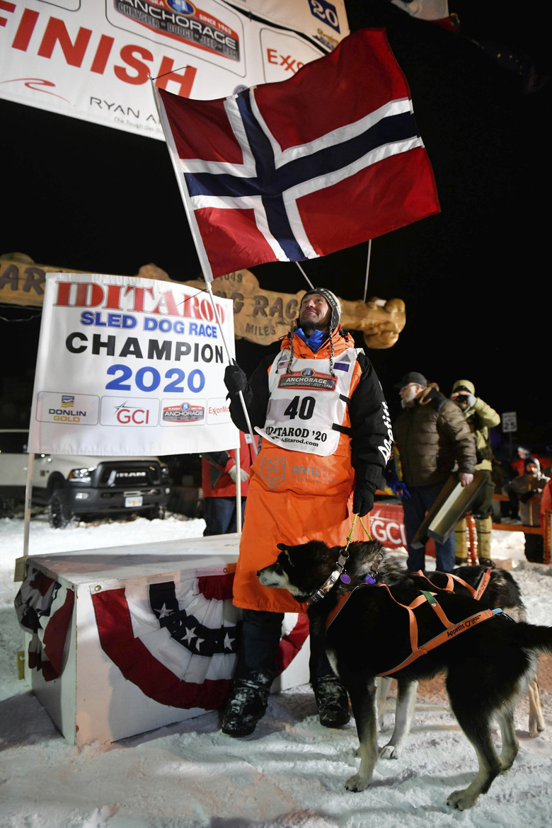 Thomas Waerner waves a Norwegian flag after winning the Iditarod Trail Sled Dog Race on March 18 in Nome, Alaska. Waerner and his dogs were stranded for 11 weeks in Alaska by  the coronavirus pandemic.  (Marc Lester/Anchorage Daily News via AP)