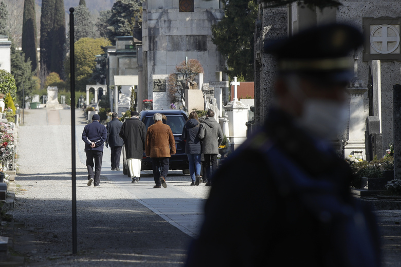 FILE – In this Tuesday, March 17, 2020. filer, relatives walk behind a hearse carrying a coffin inside the Monumentale cemetery, in Bergamo, the heart of the hardest-hit province in Italy's hardest-hit region of Lombardy, Italy. For most people, the new coronavirus causes only mild or moderate symptoms. For some it can cause more severe illness, especially in older adults and people with existing health problems. (AP Photo/Luca Bruno, File)