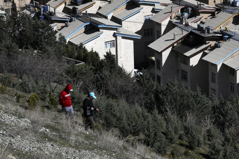 Hikers descend from a foothill of the Alborz mountain range, overlooking the capital Tehran, as they spend New Year, or Nowruz, holidays, Iran, Tuesday, March 31, 2020. In recent days, Iran which is battling the worst new coronavirus outbreak in the region, has ordered the closure of nonessential businesses and banned intercity travels aimed at preventing the virus' spread. Public parks are closed as well as sport and recreational clubs which were shut previously. (AP Photo/Vahid Salemi)